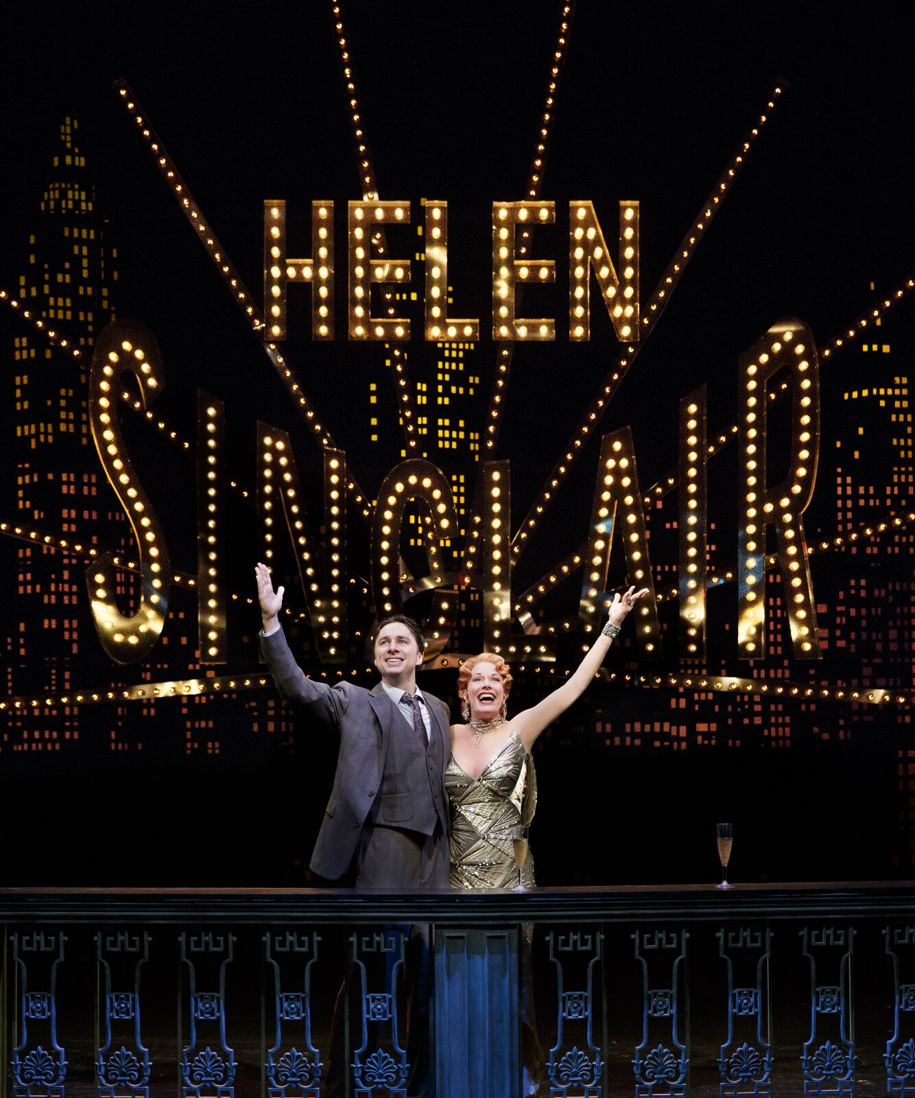 """David Shayne (Zach Braff) and Helen Sinclair (Marin Mazzie) with arms raised in front of the lit marquee of """"Helen Sinclair"""" spelled in lights."""