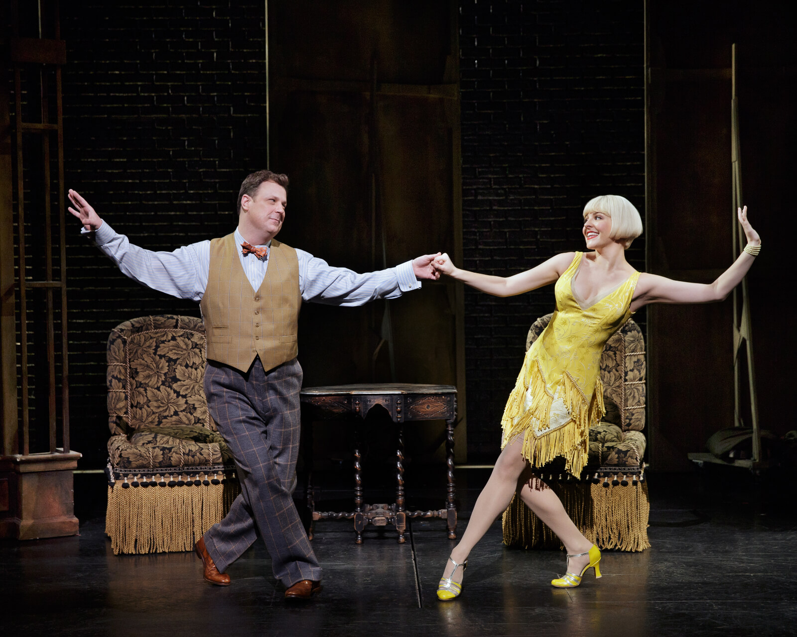 Warner Purcell (Brooks Ashmanskas in a bow tie and vest) dancing with Olive Neal (Heléne Yorke in a yellow dress).