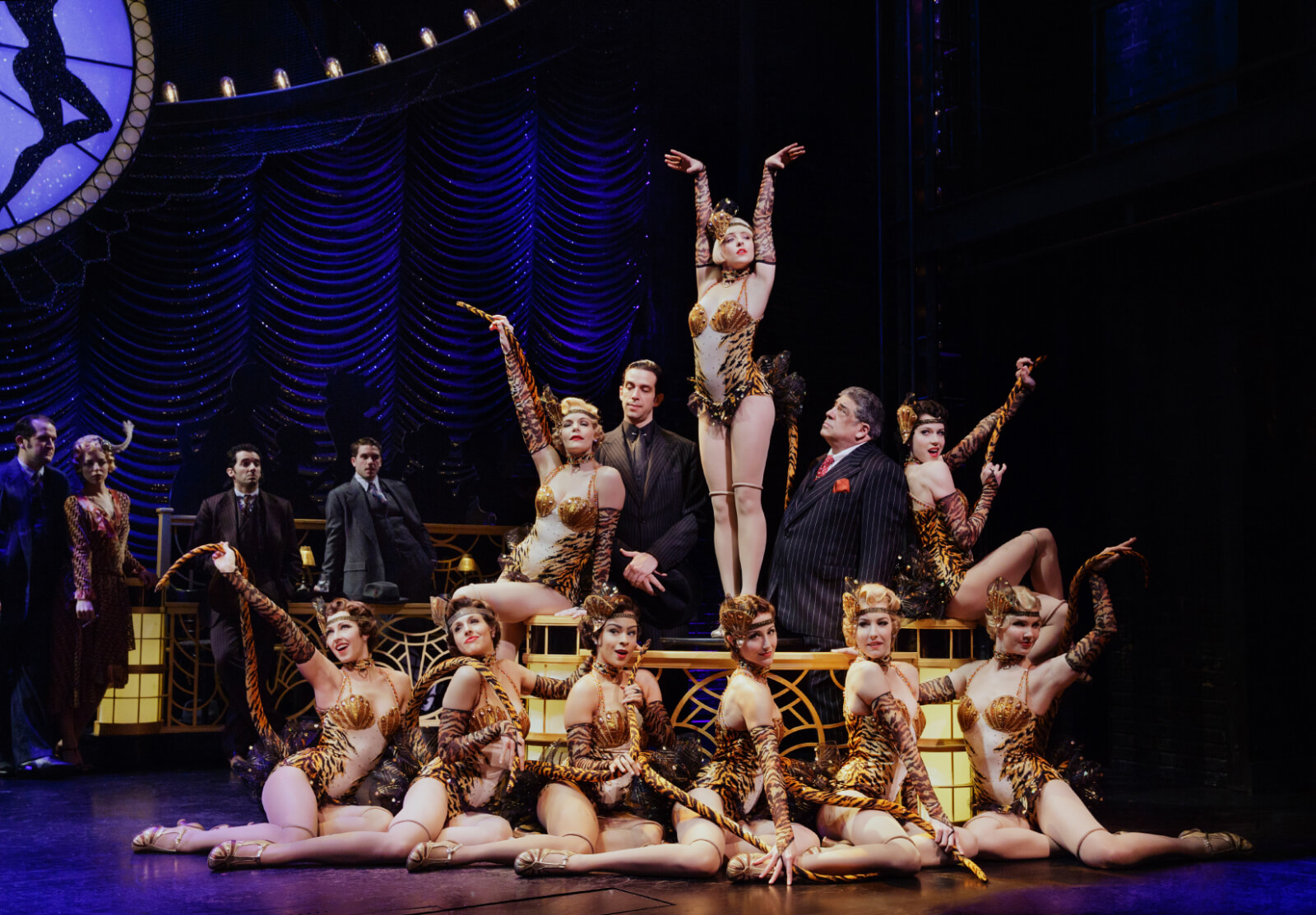 """Cheech (Nick Cordero), Olive Neal (Helene Yorke) and Nick Valenti (Vincent Pastore) and the company in """"Tiger Rag"""". Olive is center on a table surrounded by her Atta Girls with the Mob Boss looking up."""