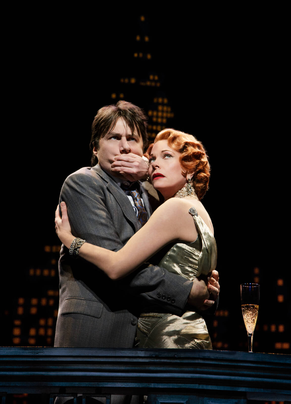 """Helen Sinclair (Marin Mazzie in a cocktail dress) hugs and covers the mouth of David Shayne (Zach Braff) with a cityscape in the background. Saying the iconic line """"Don't Speak""""."""