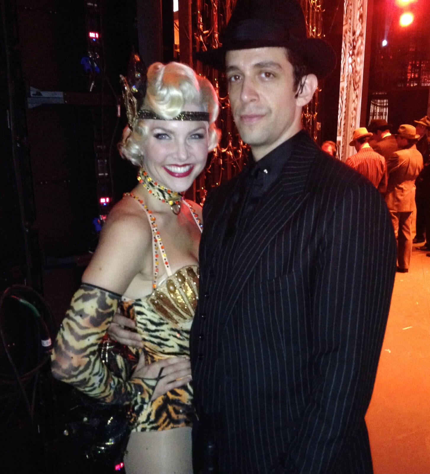 Amanda Kloots in a showgirl outfit and Nick Cordero in a black suit standing backstage in the wing.
