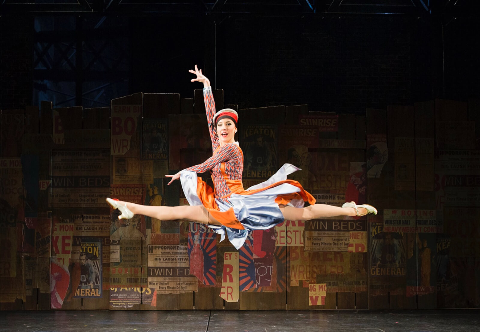 Brittany Marcin Maschmeyer dressed in a multi-colored dress does a split leap in front of a signage covered backdrop.