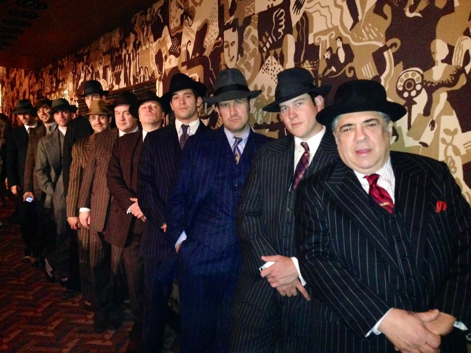 A row of 11 gangsters in pinstripe suits and hats lined up against a wall at Radio City Music Hall.