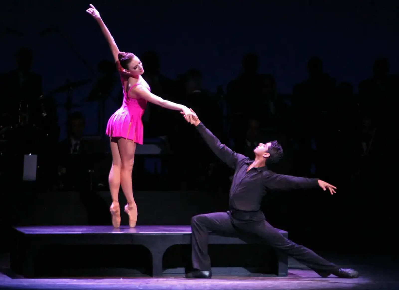 The pas de deux with Tiler Peck and Amar Ramasar continues on the bench: woman is standing on the bench en pointe while man is reaching in a lunge.