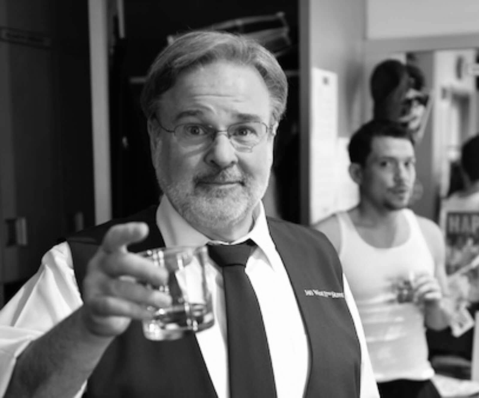 black and white photo of Fred Applegate toasting the camera with Miguel Cervantes in the background backstage.