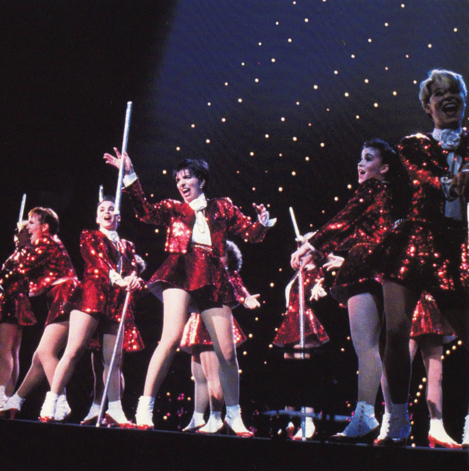 Liza and the Demon Divas. Liza and her dancers all dressed in red sequin outfits and dancing with white canes.