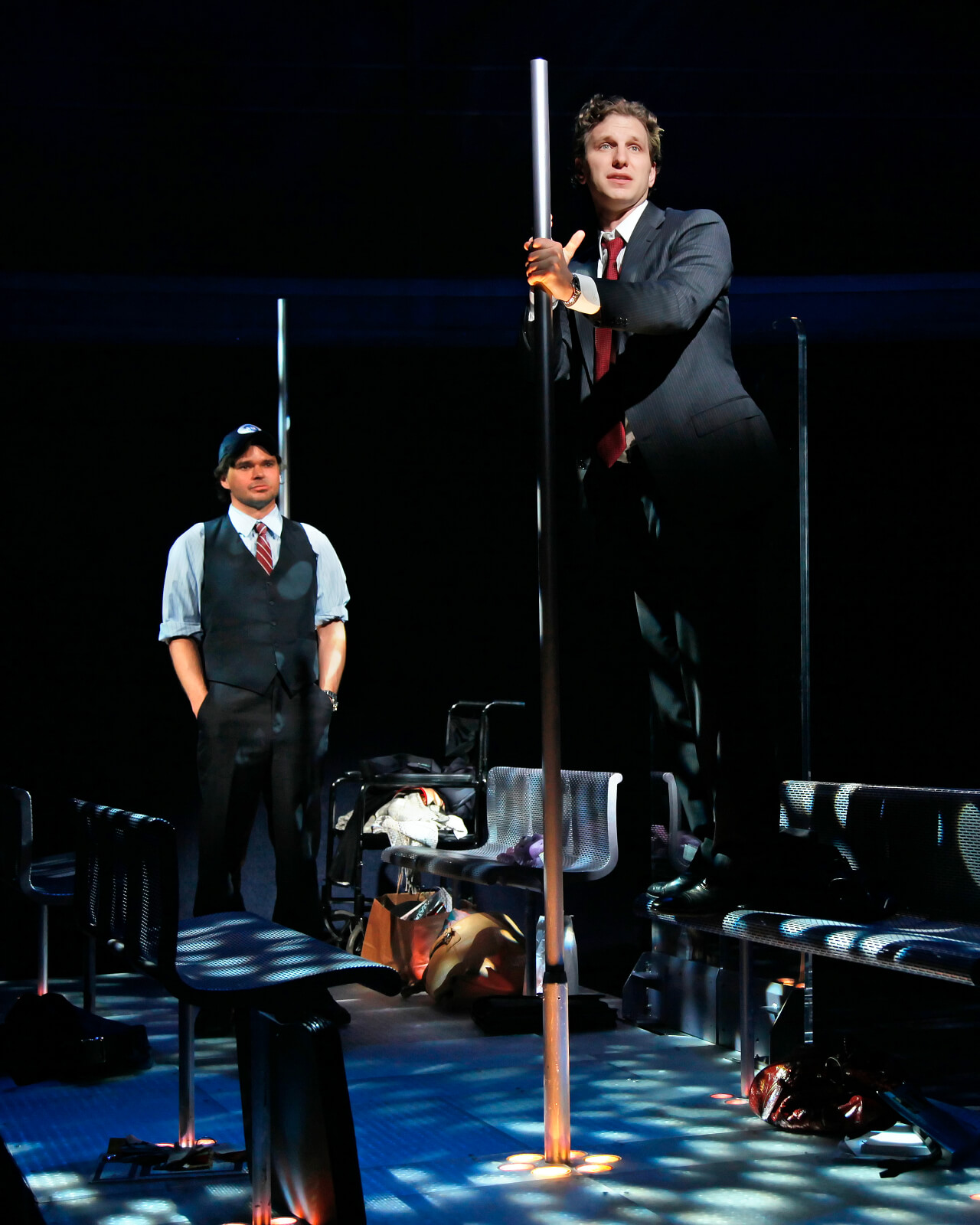 Stanley (Hunter Foster)in an MTA conductor costume looking at Zack (Sebastian Arcelus) in a suit standing on a bench