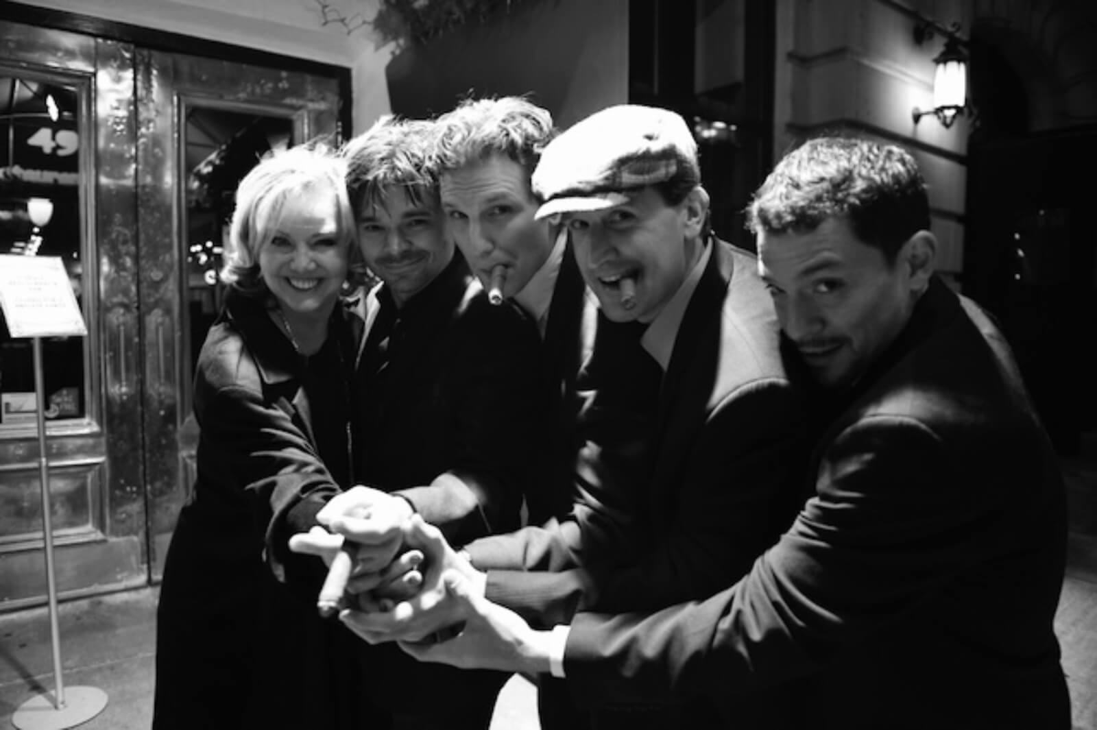 a black and white photo in front of the theater pictured left to right:Susan Stroman, Hunter Foster, Sebastian Arcelus, James Moye, and Miguel Cervantes.