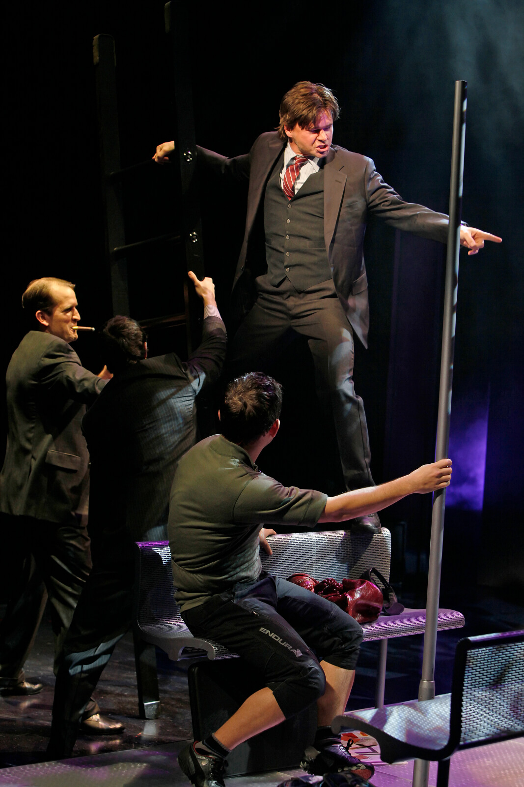 """Stanley (Hunter Foster) sings """"Step up the Ladder"""" to James Moye, Patrick Cummings and Miguel Cervantes."""