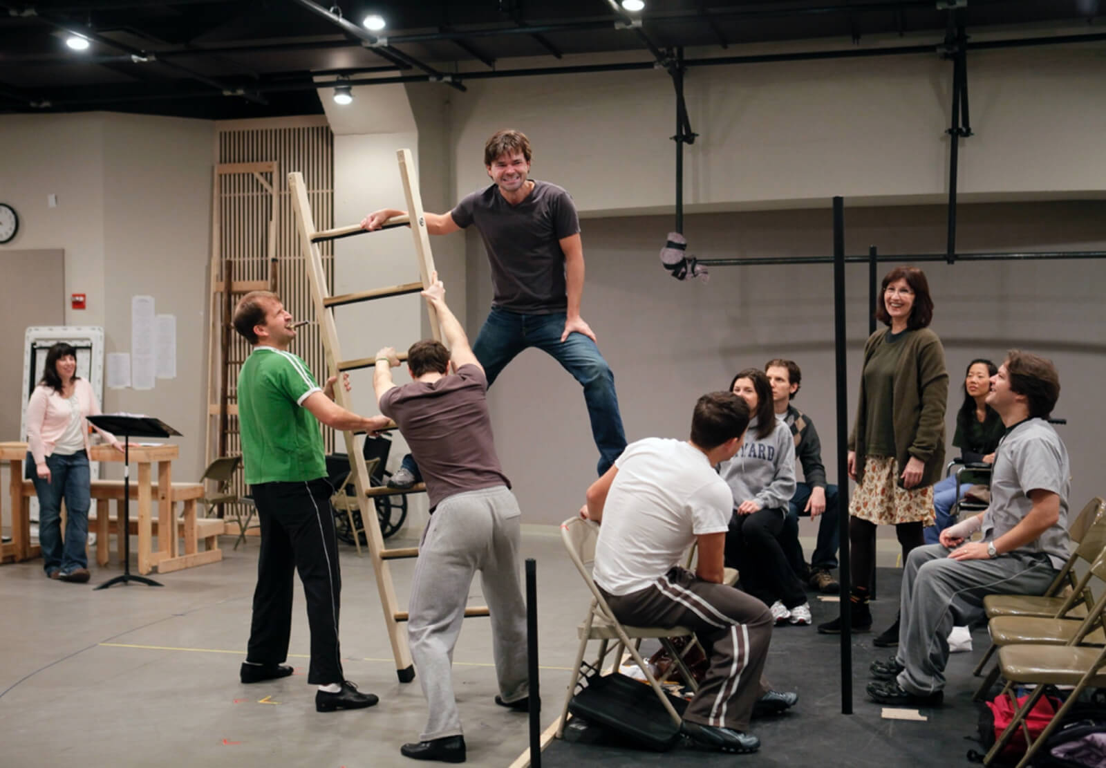 The company of Happiness works through a scene from the show involving a large ladder in a rehearsal studio