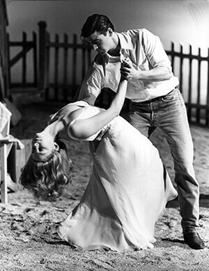 A black and white photo of Ashley Judd and Kyle Chandler doing a perfect dance dip in the yard, while being surrounded by wooden fence.