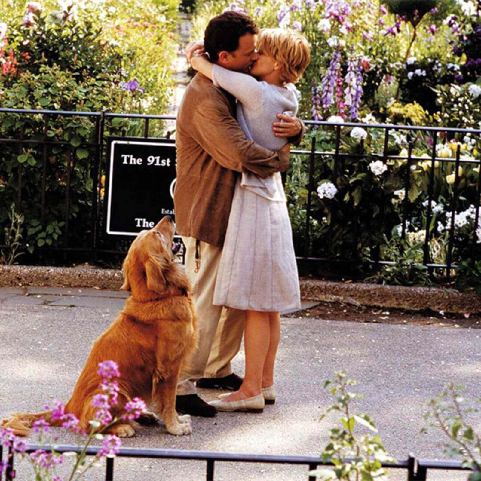 A photo of Meg Ryan and Tom Hanks in Central Park, kissing and being surrounded by beautiful flowers. His dog is watching.