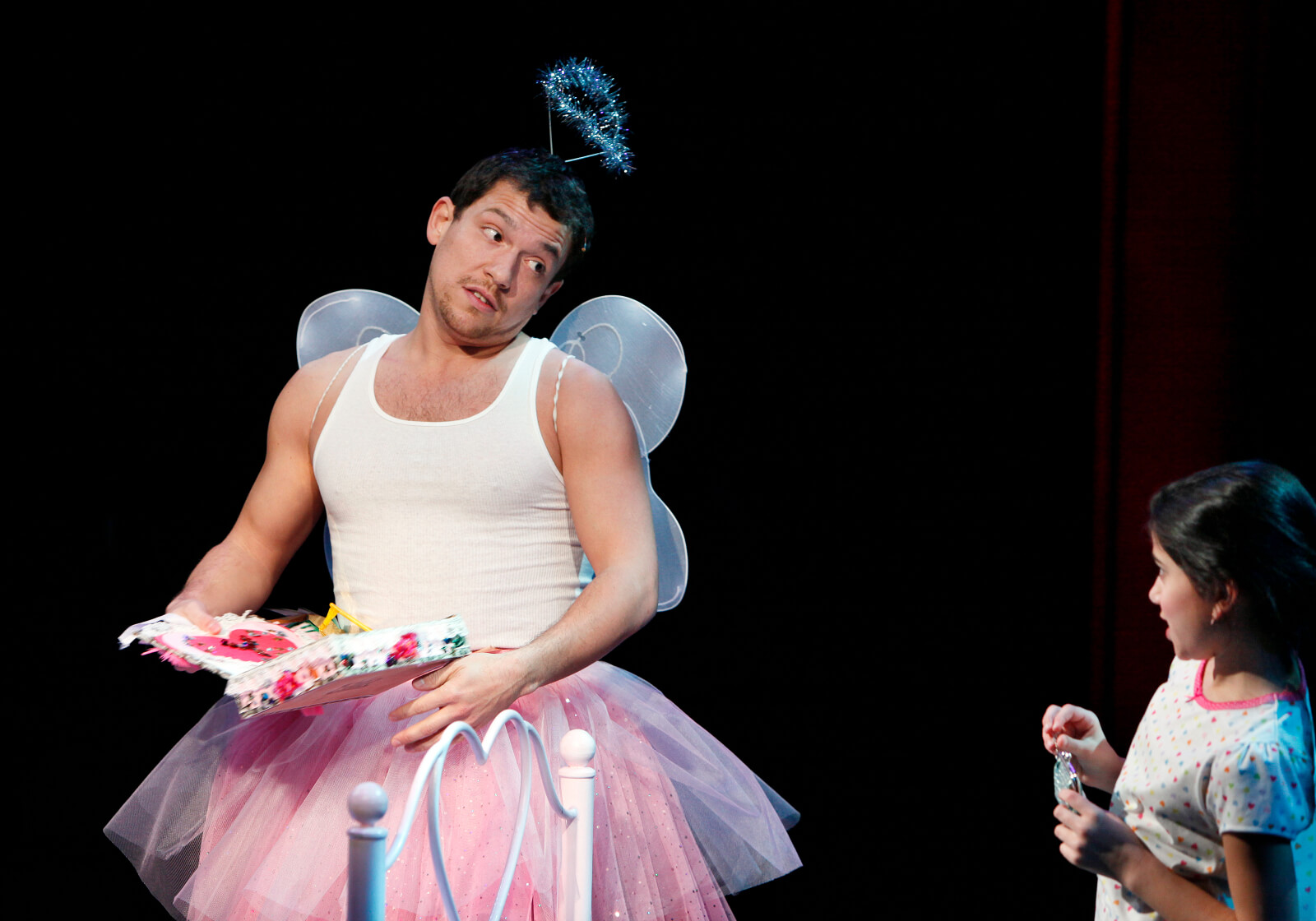 Miguel (Miguel Cervantes) in a tutu and tank top with a sparkly crown reads to a young girl, Yolanda (Lina Silver) from a colorful book.