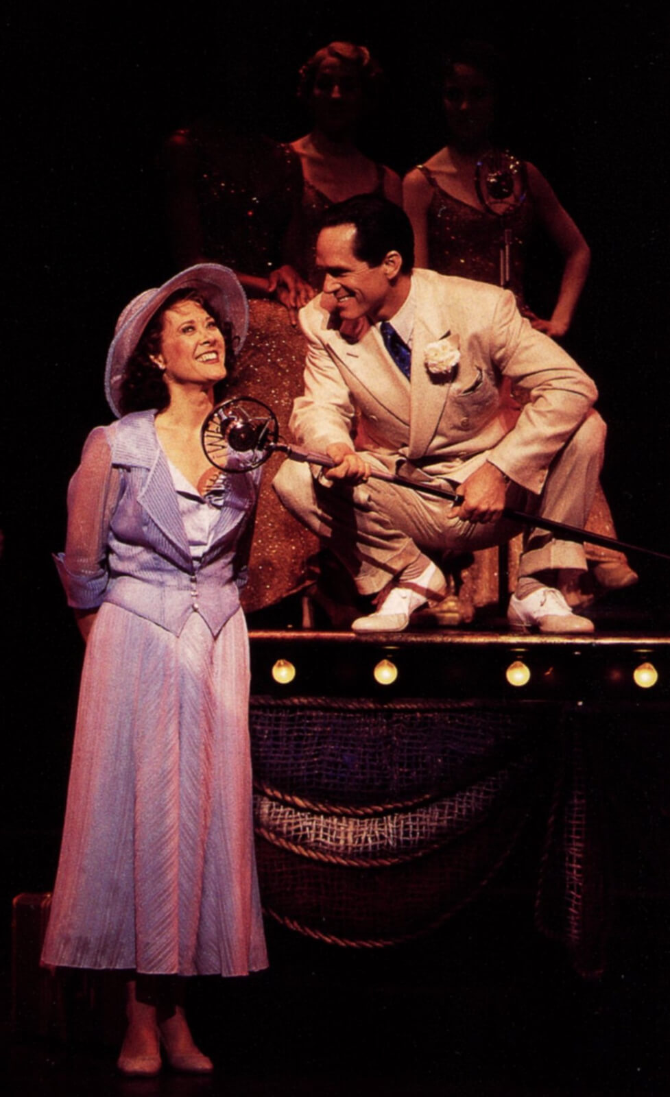 Rita Racine (Karen Ziemba in a blue sun dress and hat) and Mick Hamilton (Gregory Harrison on a platform with microphone, squatting with microphone to speak to her and make sure she is heard).