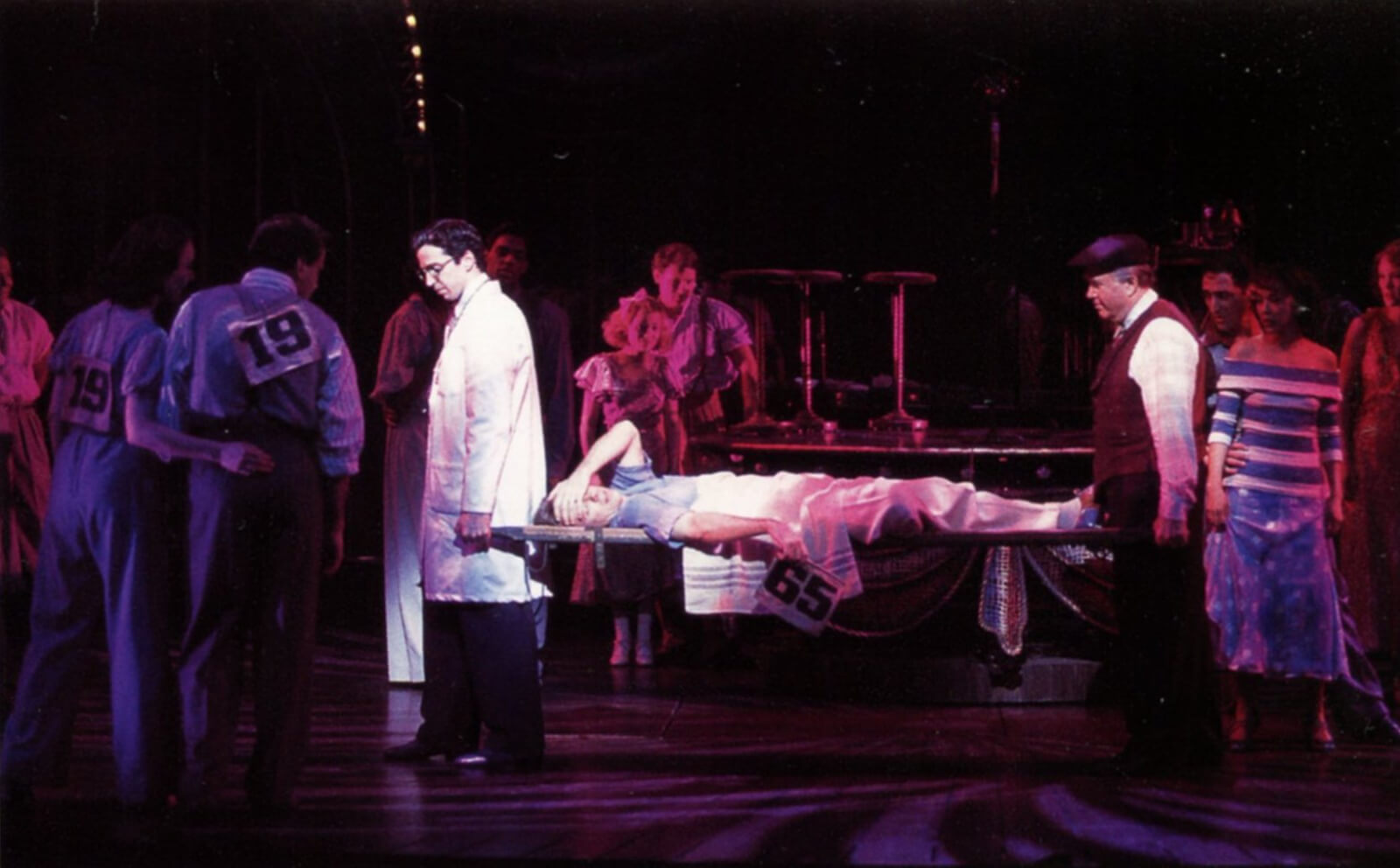 Man is carried out on a stretcher, exhausted, but still holding his dance card, which is #65.
