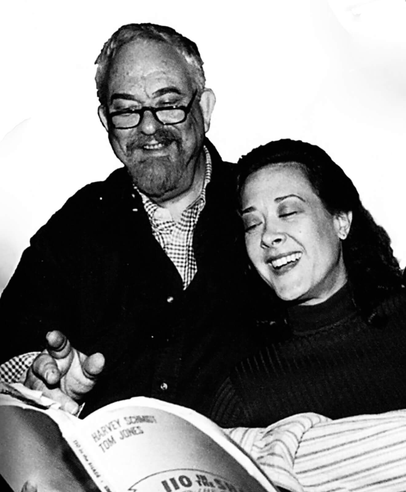 Black and white photo of Harvey Schmidt and Karen Ziemba in rehearsal. Both standing over sheet music, while Karen is singing and Harvey looks on smiling.
