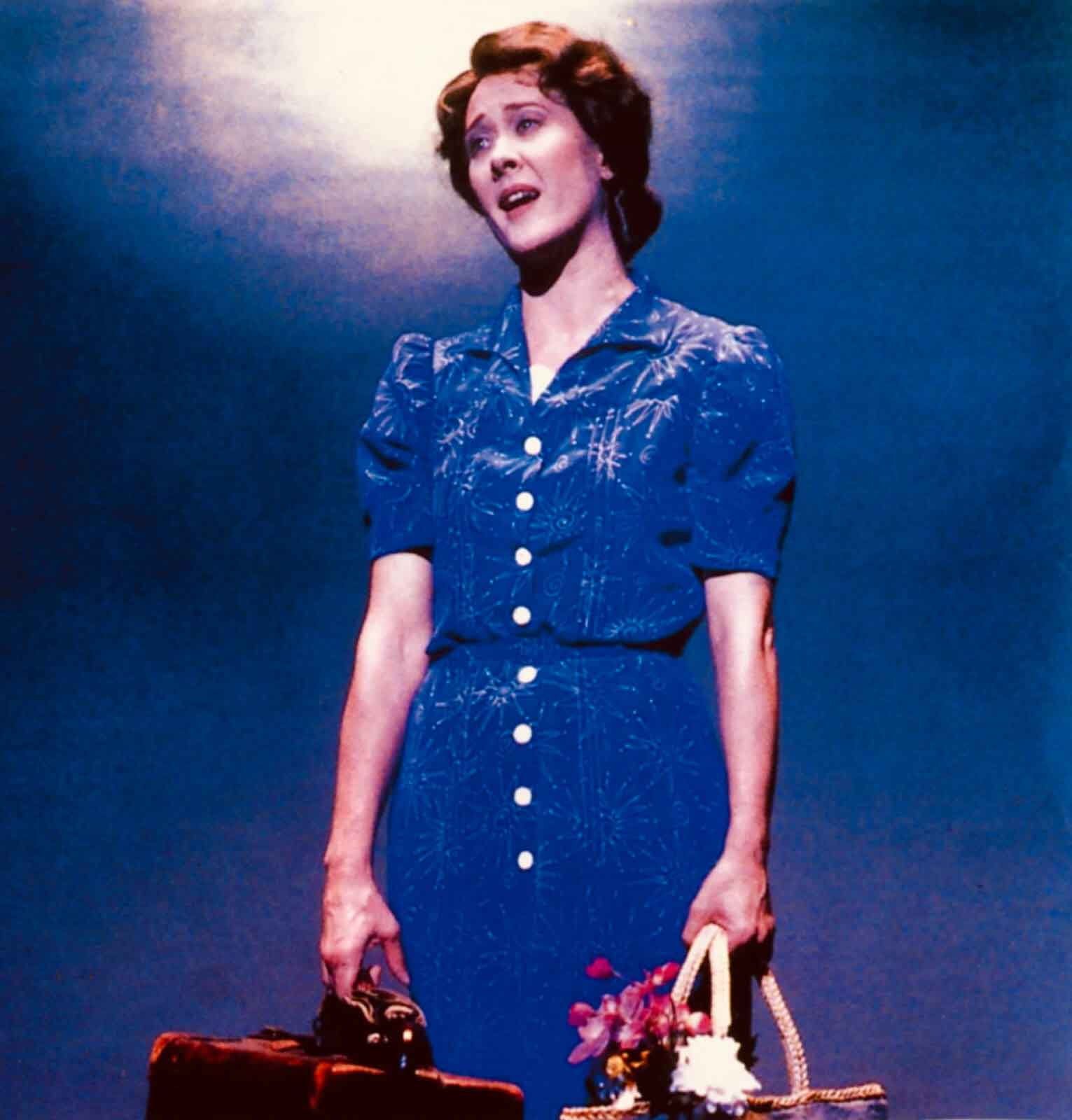 """Karen Ziemba as Lizzie singing """"Simple Little Things"""". She wears a button down blue dress with puffy sleeves, holding luggage and a basket with flowers."""