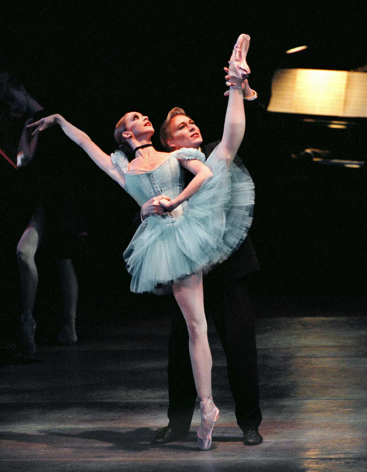 Maria Kowroski and Robert La Fosse dance a pas de deux as he holds her leg in the air. She is in a blue dega-like tutu.