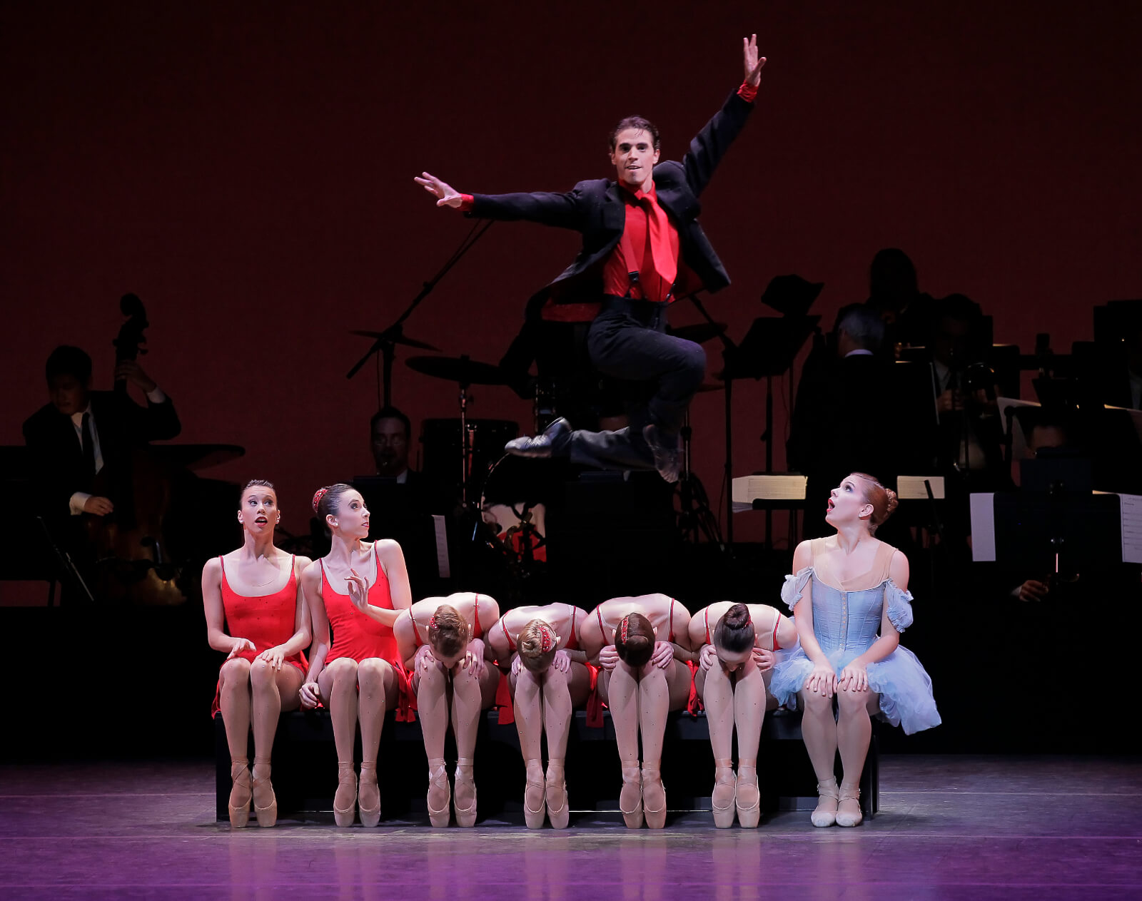 """Sébastien Marcovici leaps over the flappers in """"It Don't Mean a Thing if it Ain't Got That Swing"""". He is dressed in a black suit with a bright red tie."""