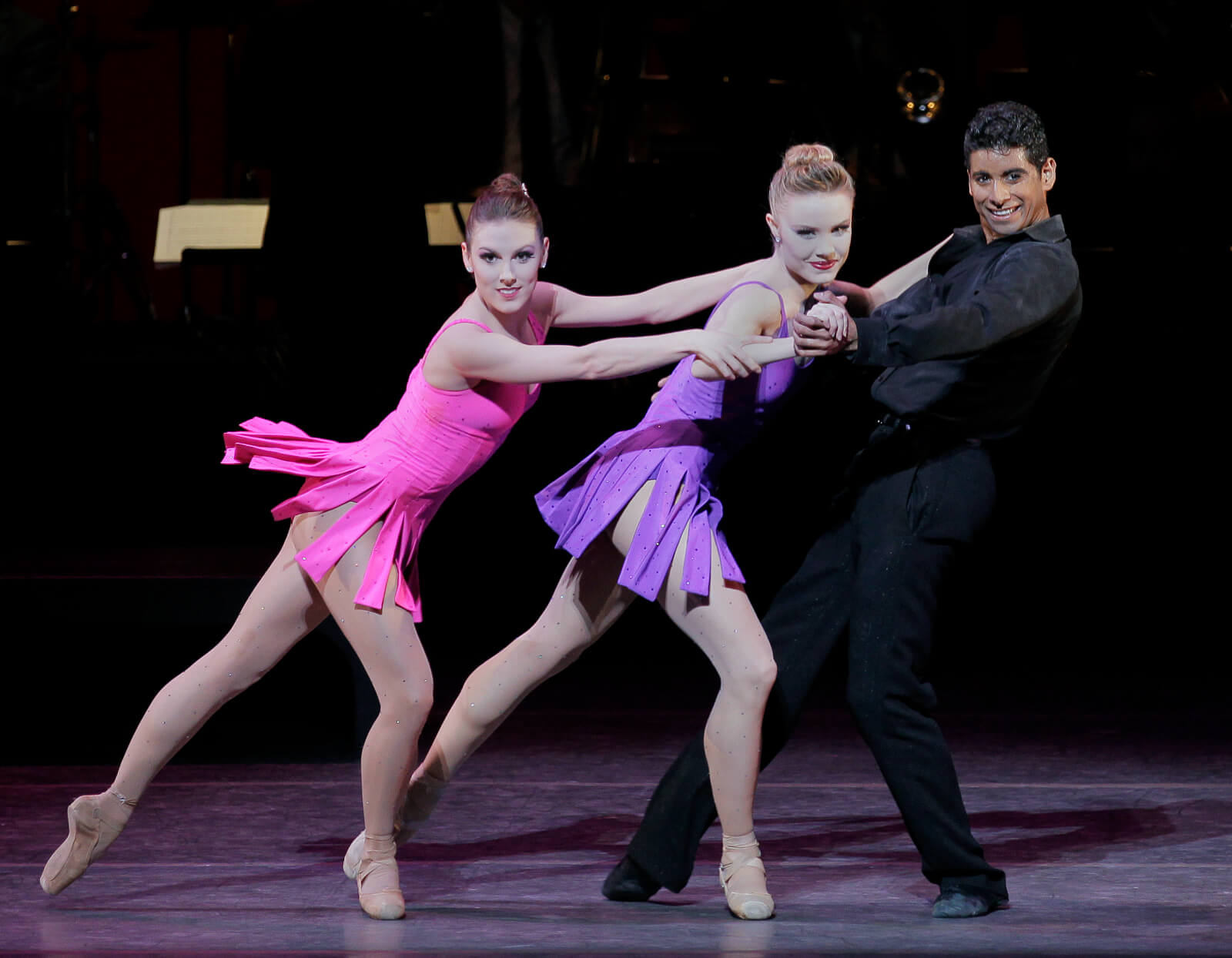 World premiere of For the Love of Duke: two women, Tiler Peck in pink and Sara Mearns in purple, dance with Amar Ramasar, dressed in all black.