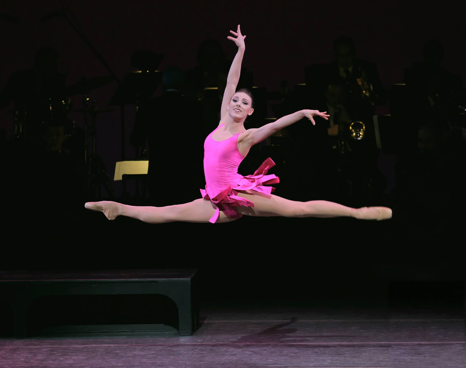 Tiler Peck (dressed in pink) in a grand jeté leaps through the air.