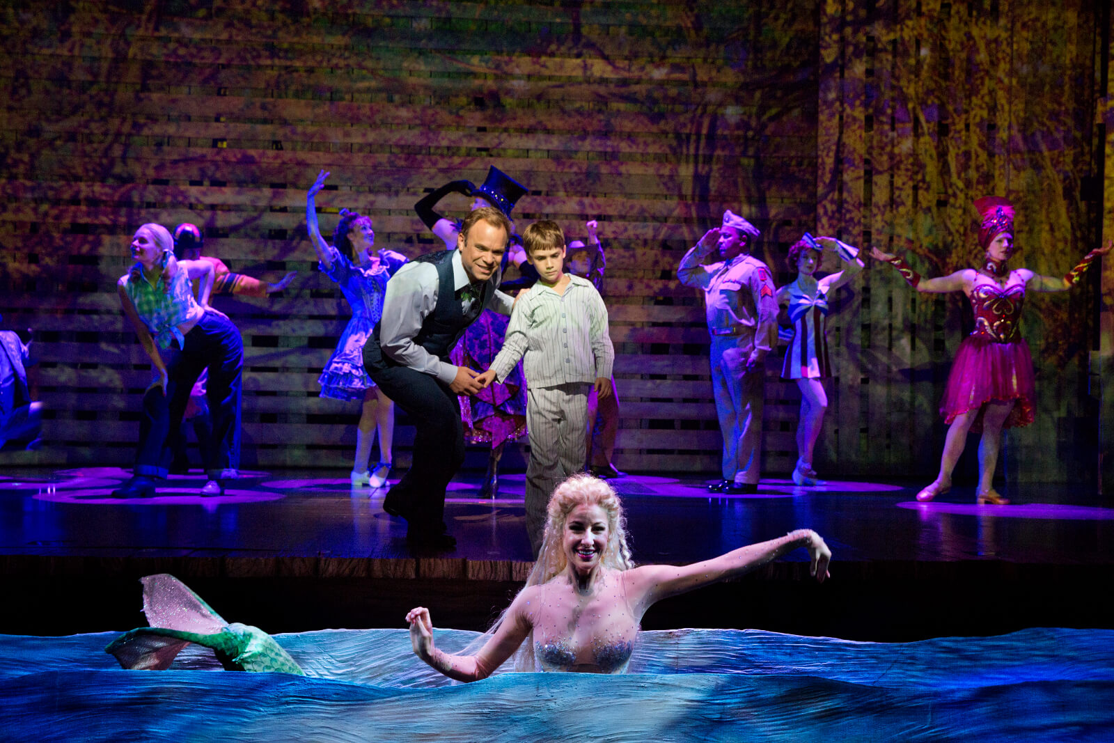 Edward Bloom (Norbert Leo Butz) shows Young Will (Zachary Unger) the mermaid (Sarrah Strimel). The mermaid appears from the water.