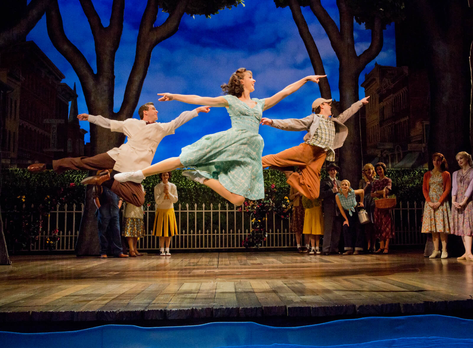 """Jason Lee Garrett, Lara Seibert Young, and Cary Tedder performing """"Out There on the Road"""". The trio leaps in unison onstage."""