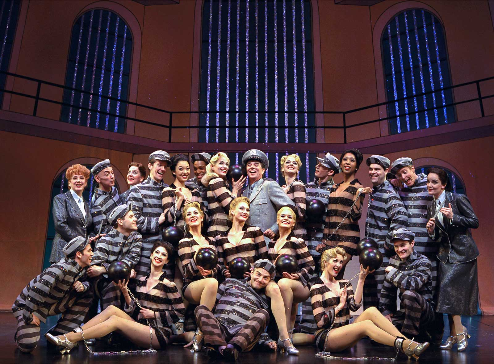 """Cady Huffman, Gary Beach, and the Original Broadway Cast of The Producers in """"Prisoners Of Love"""". All are dressed in jail costumes with head warden and two matrons."""