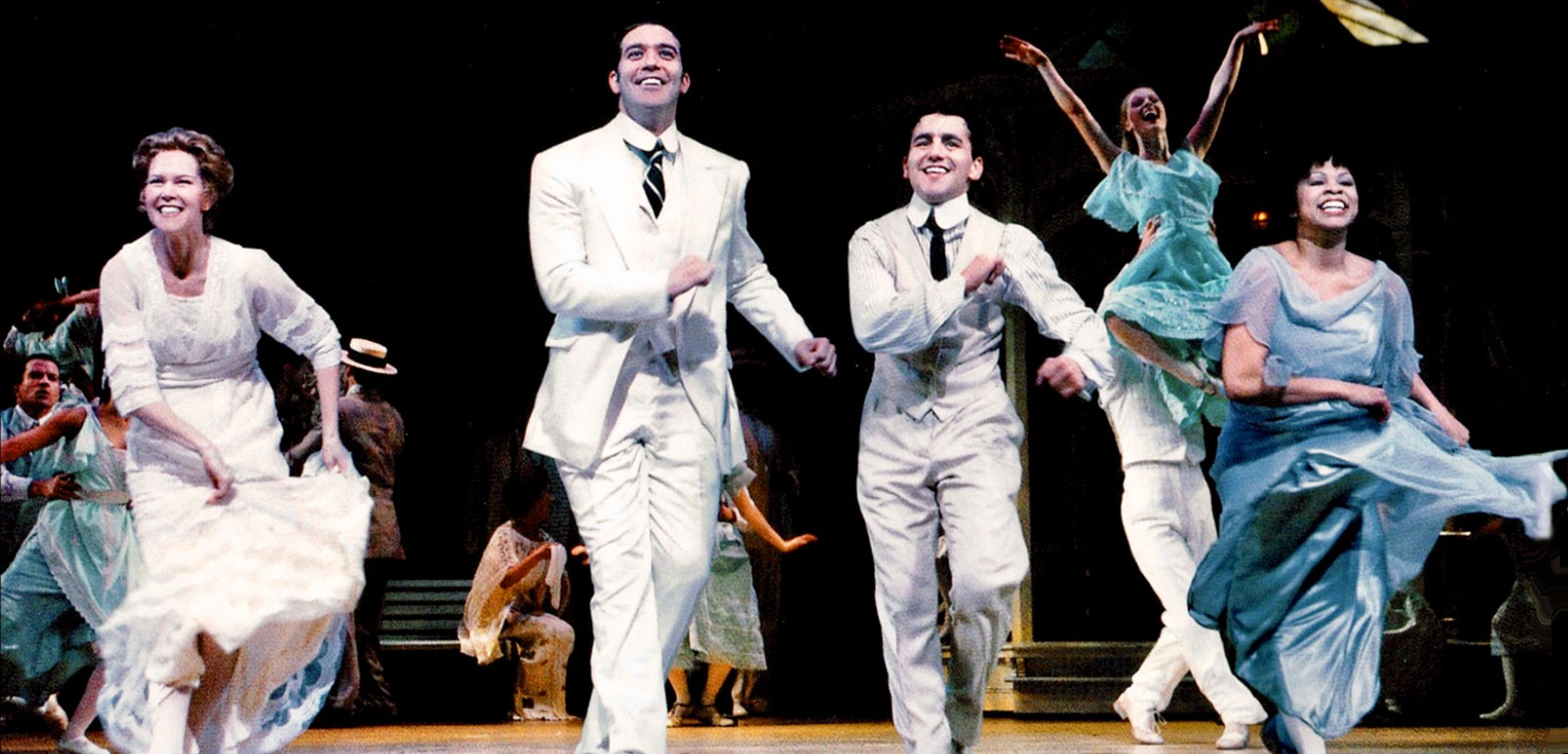 """Rebecca Luker (Marian Paroo), Harold Hill (Craig Bierko), Marcellus Washburn (Max Casella) and Ethel Toffelmier (Tracy Chapman) dancing """"Shipoopi"""". The men are dressed in handsome white suits and the women are in beautiful dresses."""