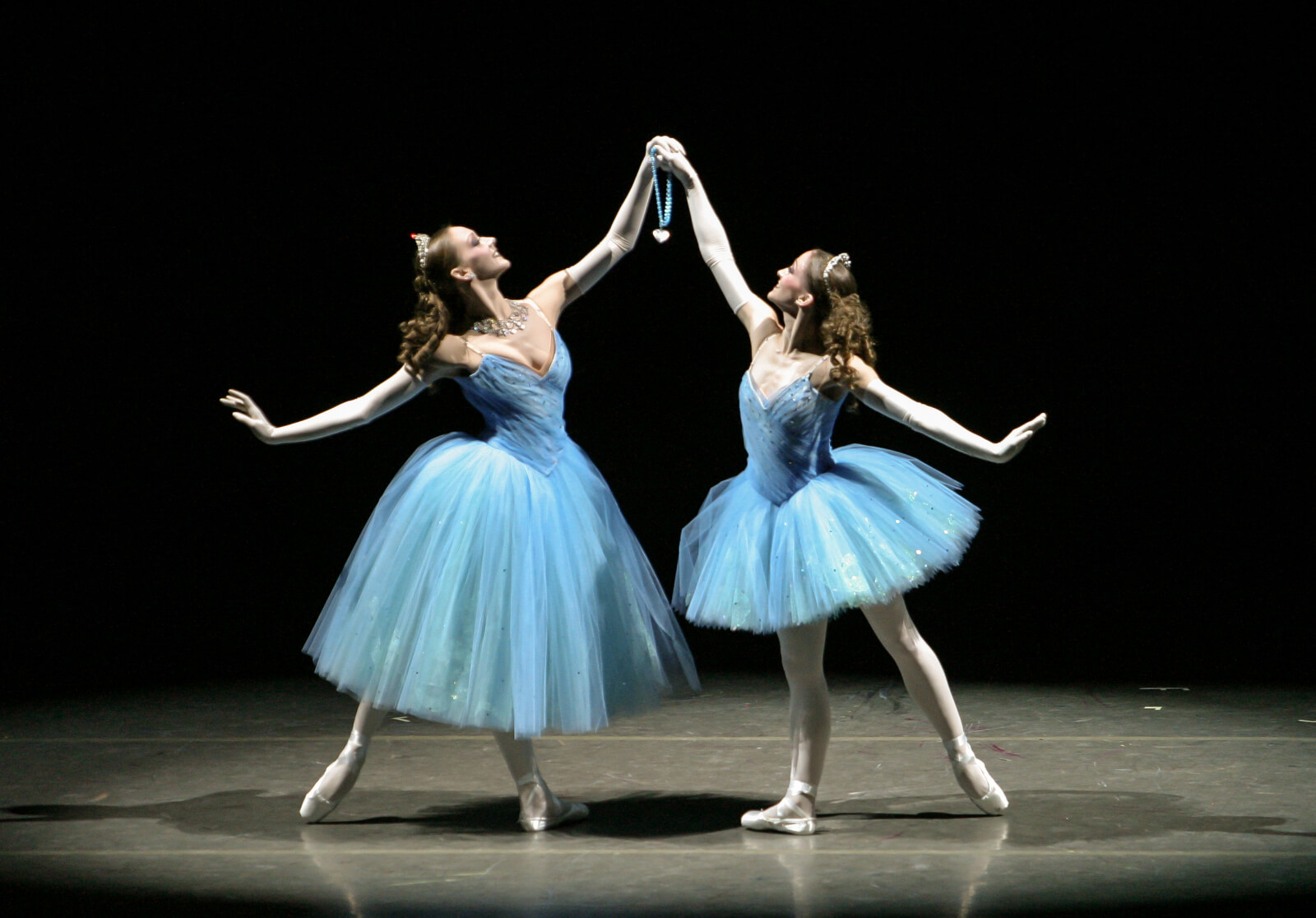 Maria Korowski and Ashley Bouder (both in blue tutus) with the Blue Necklace held in the air between them.