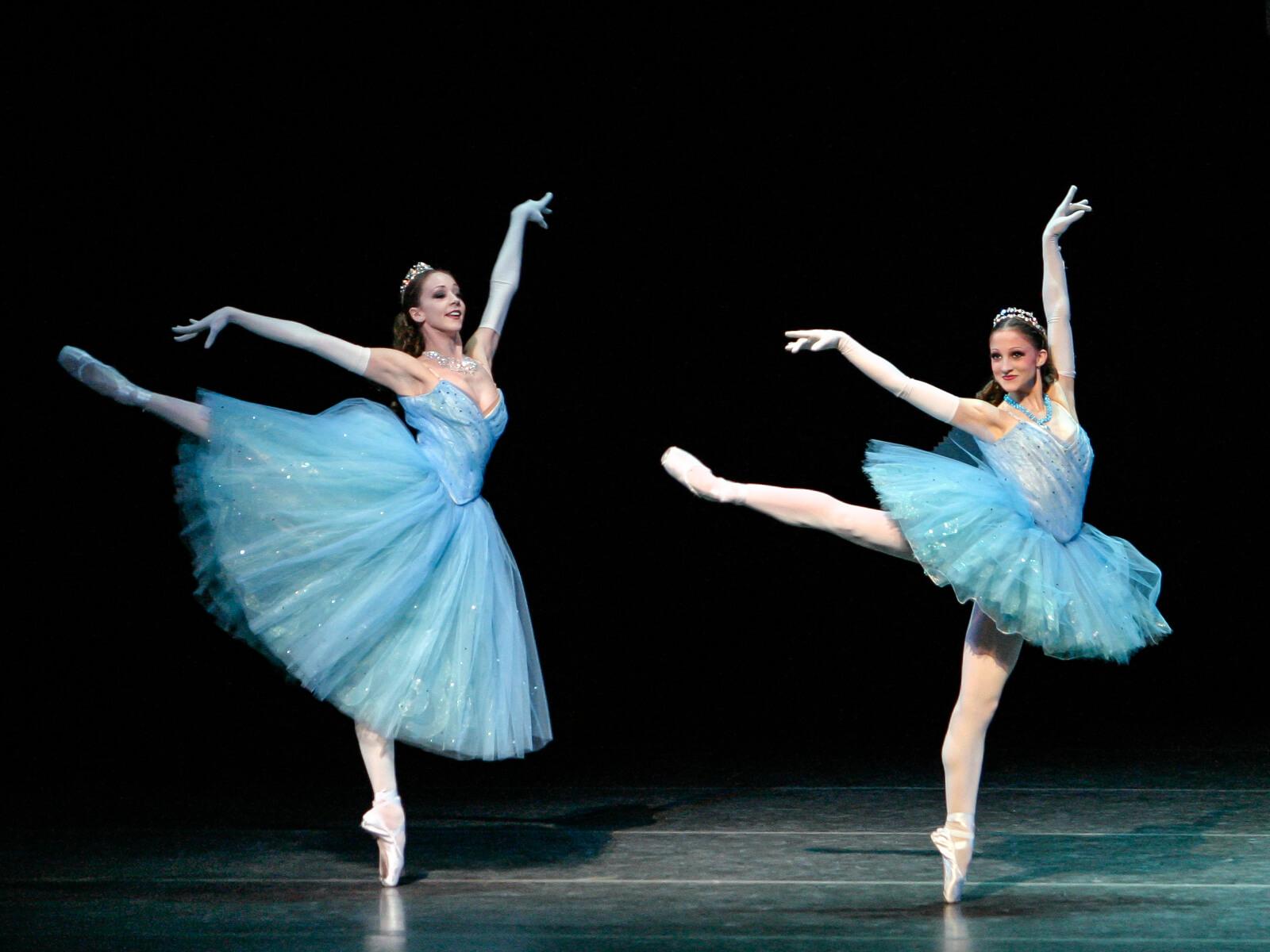 Maria Korowski and Ashley Bouder (both in blue tutus) dance in a pas de deux, captured in a back attitude en pointe.