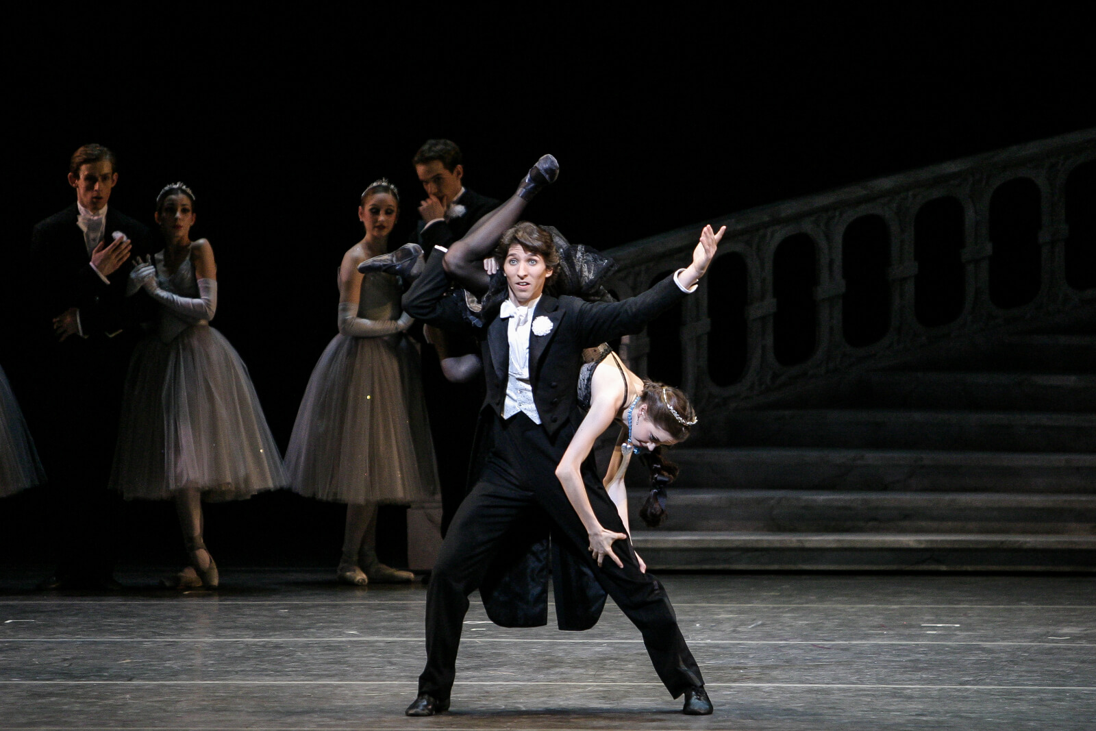Damian Woetzel and Megan Fairchild in a comedic pas de deux: Megan is held by one leg on his back, while grabbing his leg.