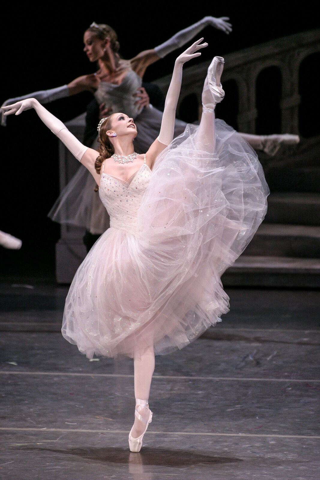 Maria Korowski in a solo moment, en pointe with a grand battement.