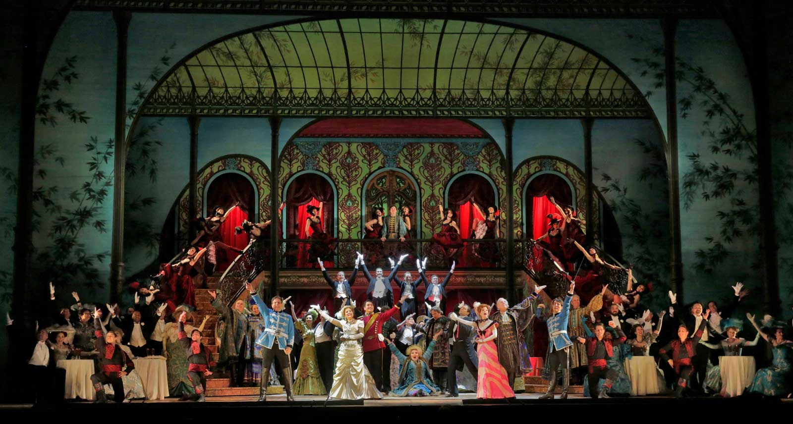 The Merry Widow cast pose for the grand finale. They are dressed in gorgeous gowns and Parisian suits.
