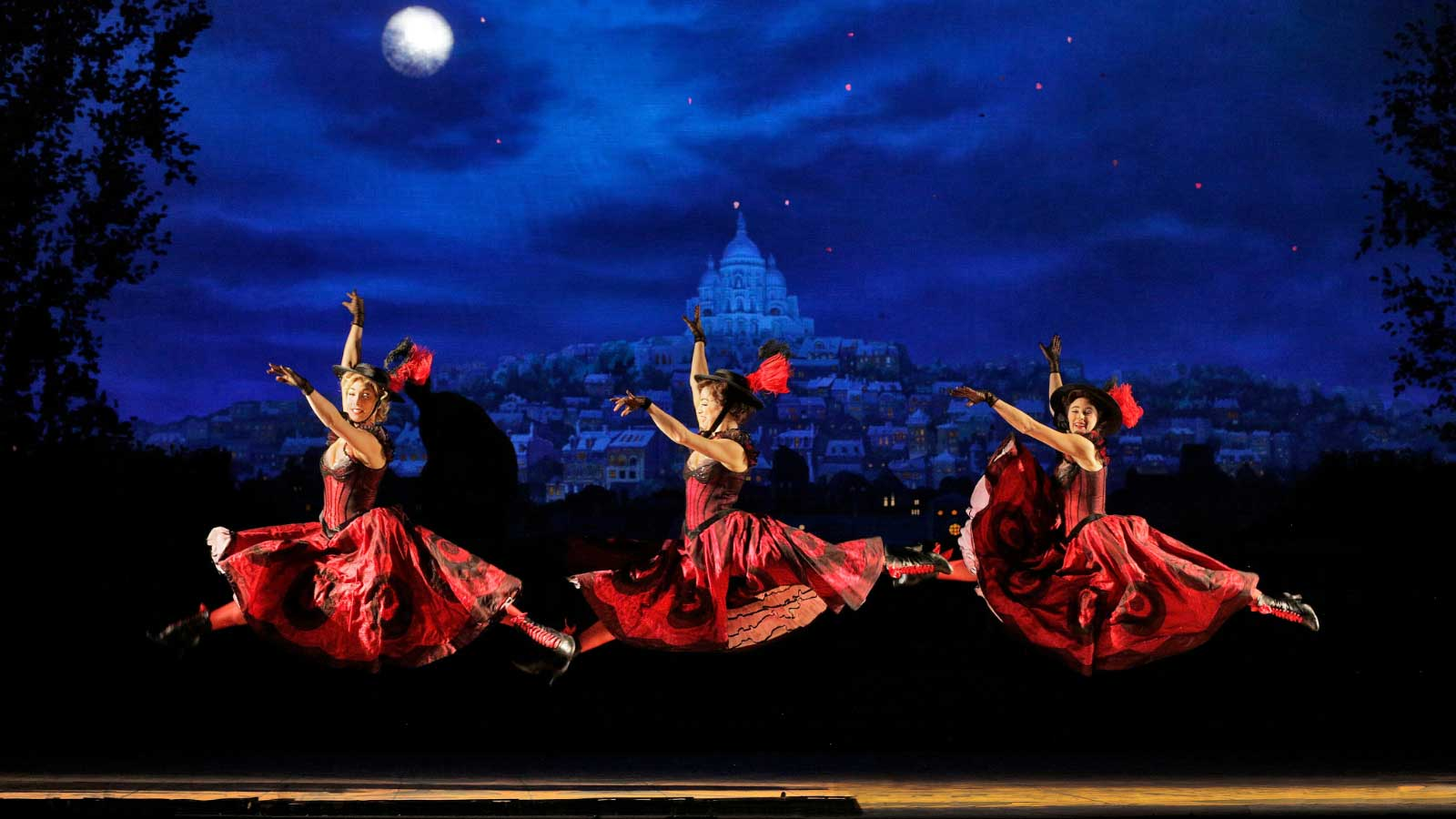 Erin Monteleone, Emery LeCrone and Kristen Schoen-Rene doing a jete in the air wearing their Red and Black Can Can dresses. There is a view of Paris at night behind them.