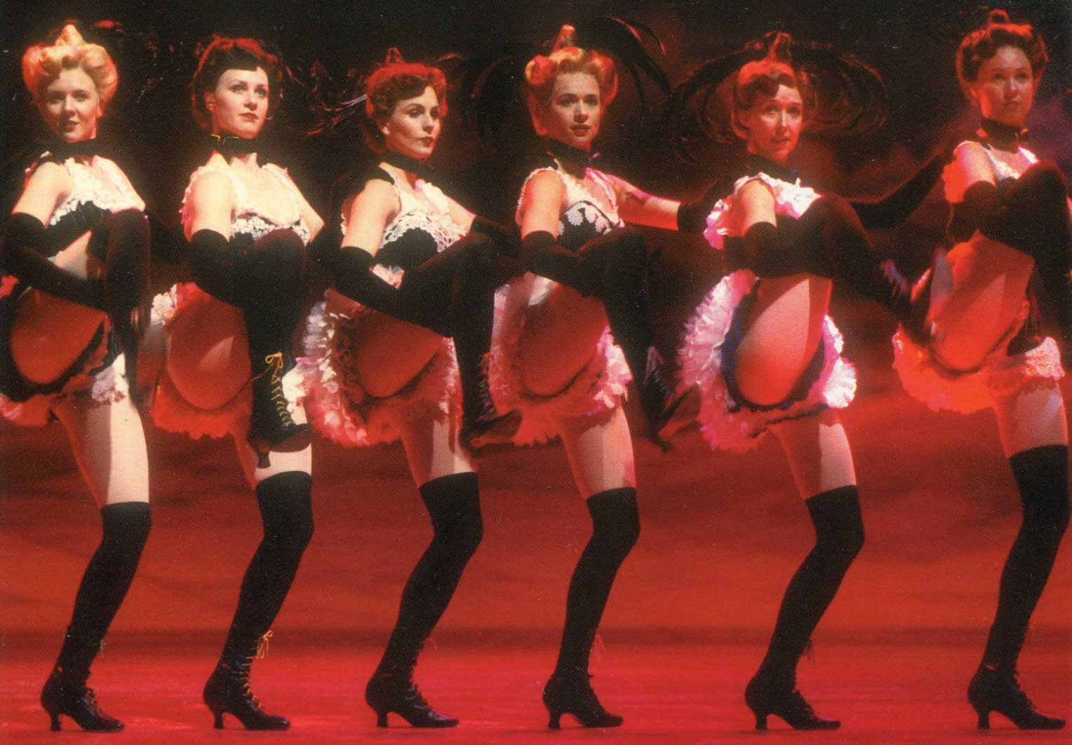 The Dream Ballet Postcard Girls wearing black high boots and white and black lacy outfits, doing a can can dance.