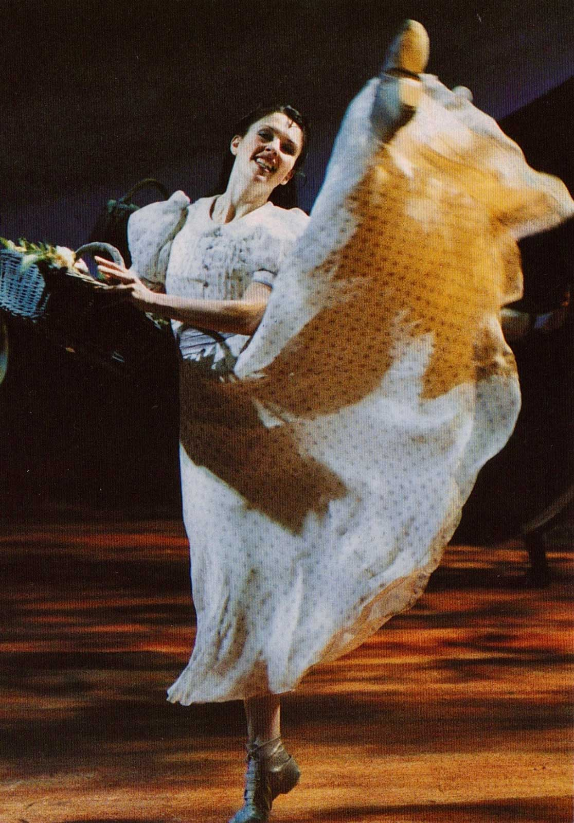 Laurey Willians (Josefina Gabrielle) in a white polkadot dress, dancing with her leg up while holding a basket of goods.