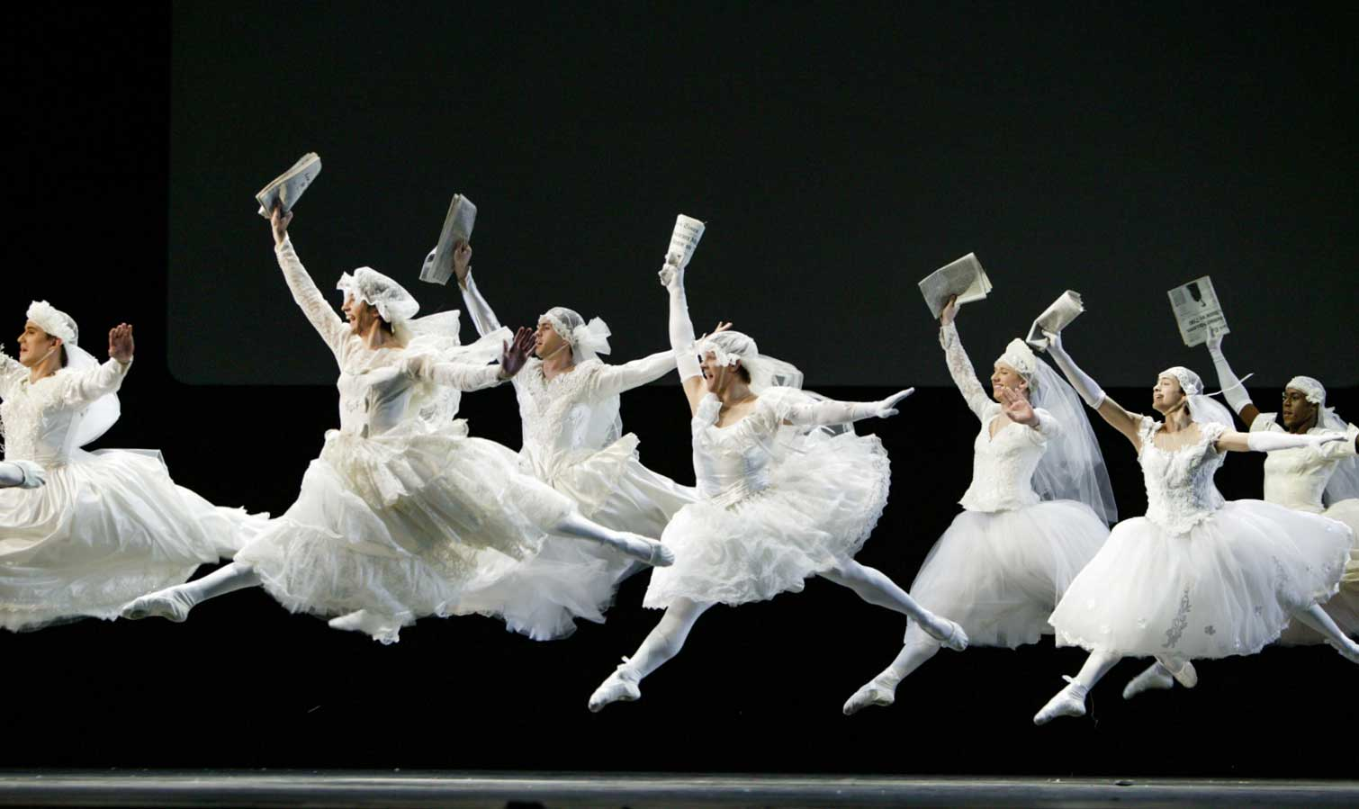 A group of brides all in white (some men dressed as women) leap at the news, held in their upstage hand.