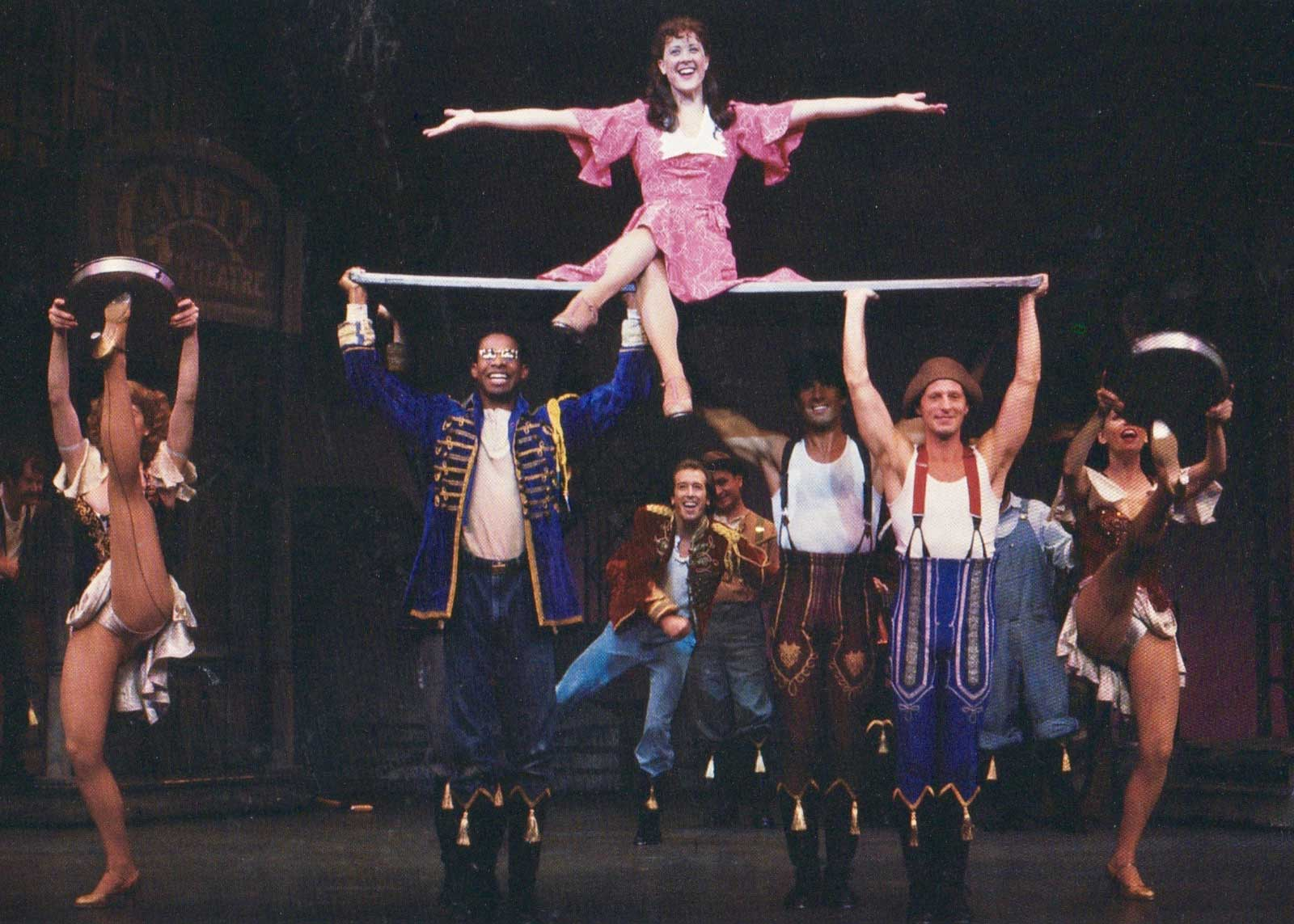 """Polly Baker (Karen Ziemba) opens her arms out wide and sits on a plank that is lifted by three men in the musical number """"I Got Rhythm"""""""