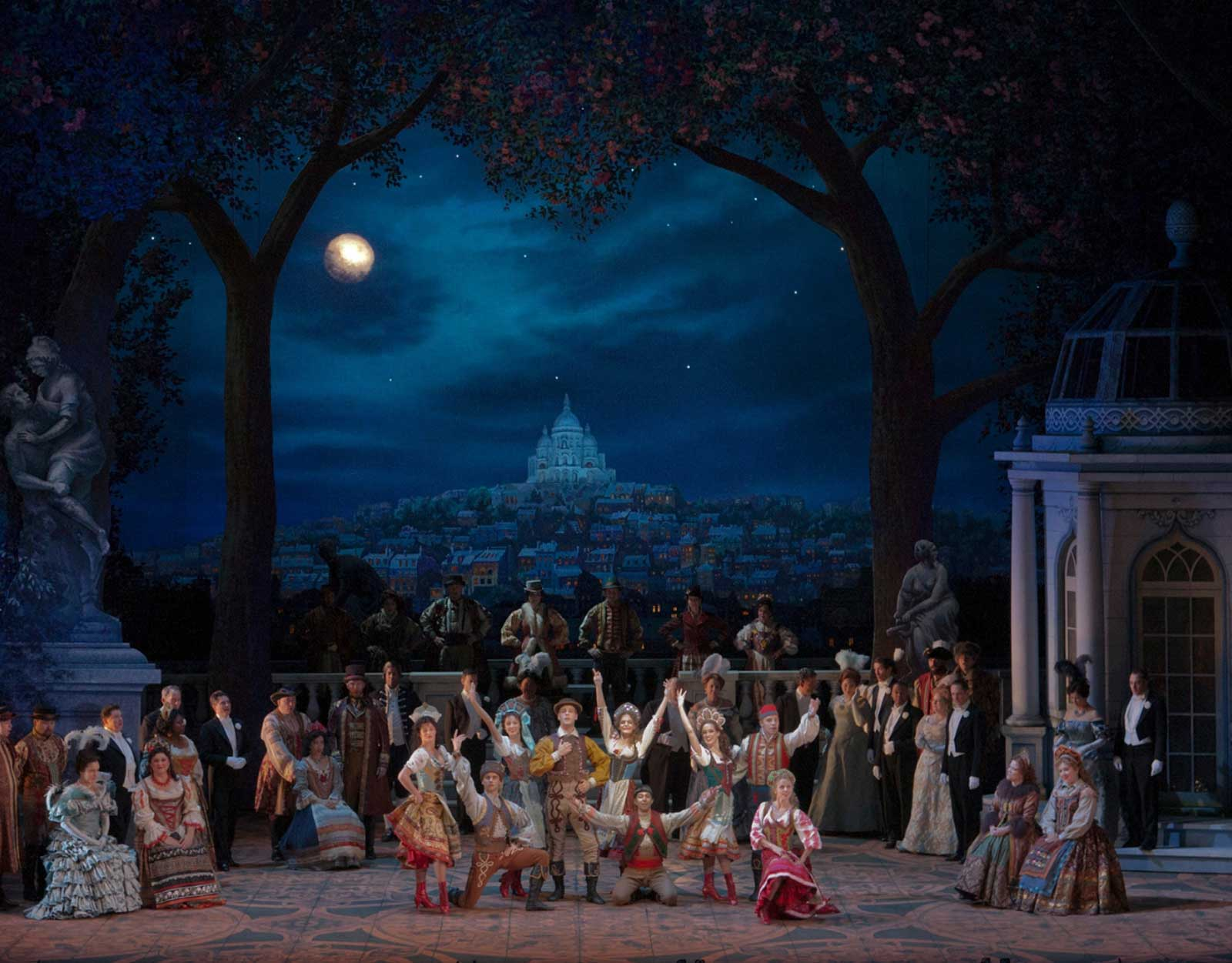 The cast performs a Pontevedrian Folk Dance in Hanna's Garden. There are in traditional kolo dance costumes. There is a view of Paris in the background. There is a full moon.