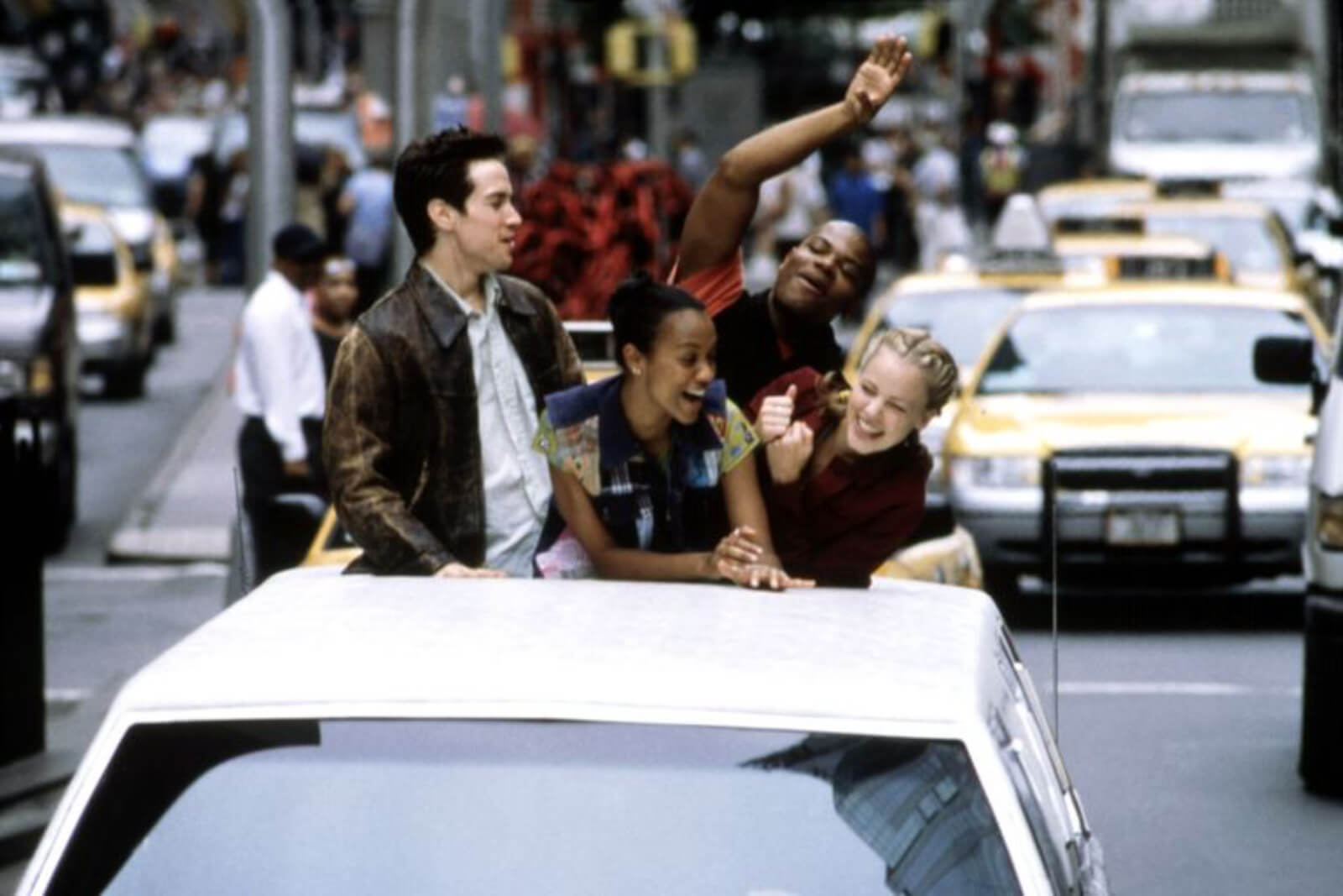 Sascha Radetsky, Zoe Saldana, Shakiem Evans, and Amanda Schull popping out the top of a sun roof in NYC traffic.