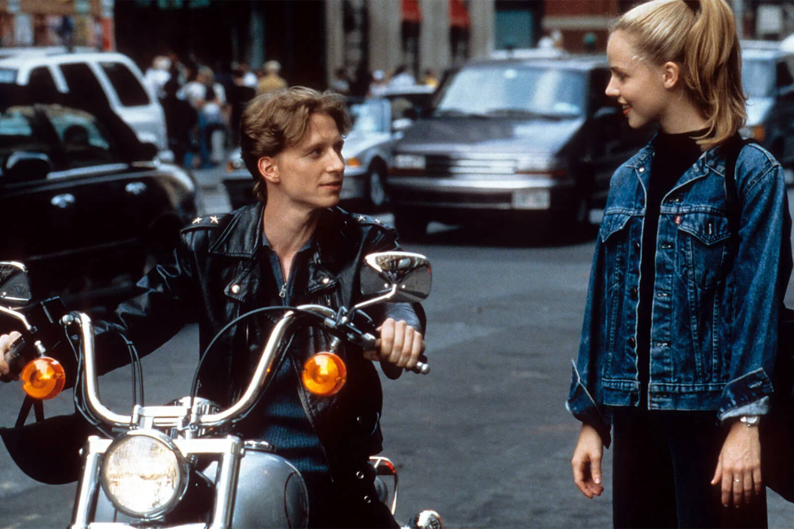 Ethan Stiefel (on motorcycle) speaking to Amanda Schull (standing on street).