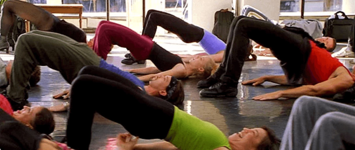 Amanda Schull taking jazz dance class, in a boat pose (pelvis up) with other dancers.