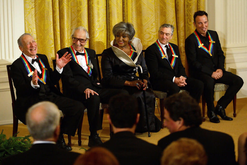 Recipients of the 2009 Kennedy Center Honors: Mel Brooks, Dave Brubeck, Grace Bumbry, Robert DeNiro, and Bruce Springsteen. All are seated in black tie with the award (in signature rainbow ribbon) around their necks and Mel is laughing.