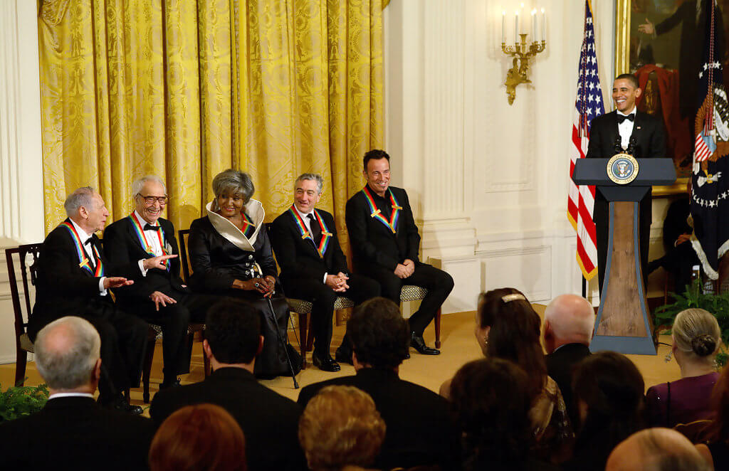 2009 Honorees Mel Brooks, Dave Brubeck, Grace Bumbry, Robert DeNiro, and Bruce Springsteen with President Barack Obama in the East Room. Mel is sharing a joke with Obama (at the podium) who is smiling.