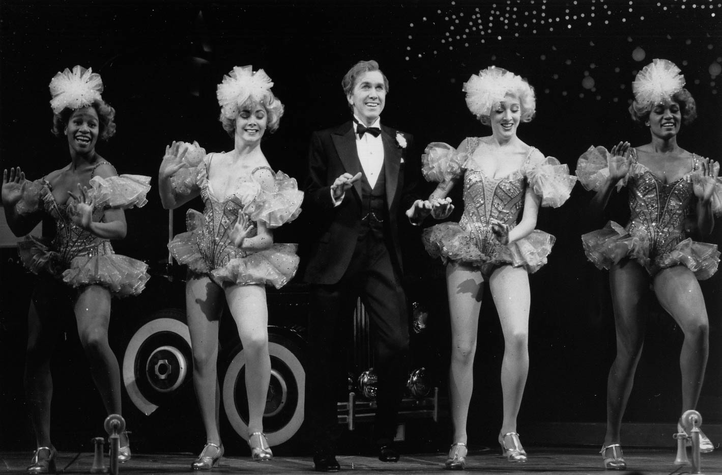 """Black and white photo of Harry Groener (in a tux) and the female ensemble (dressed in frilly pink costumes). Judine Hawkins Richard, Ida Henry, Harry Groener, Jean Marie, Salome Mazard dance to """"I Can't Be Bothered Now""""."""