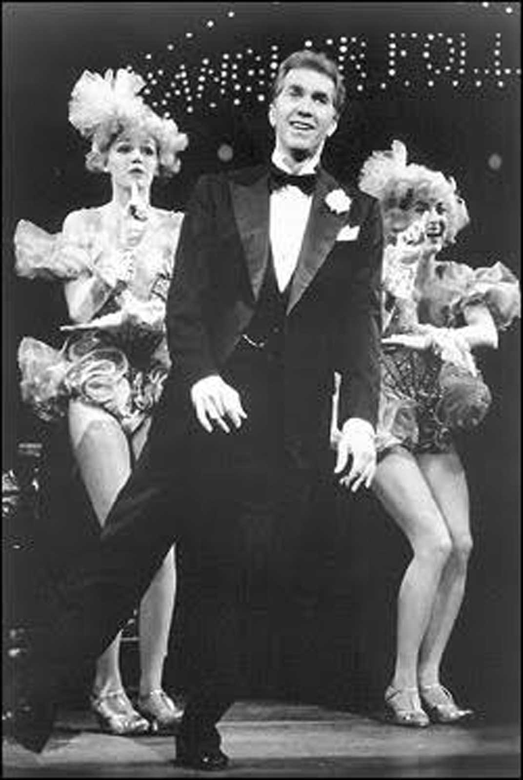 Black and white photo of Harry Groener (in a tux, tap dancing and leaning sideways) with Penny Ayn Maas and Paula Leggett (also tap dancing in frilly pink costumes).