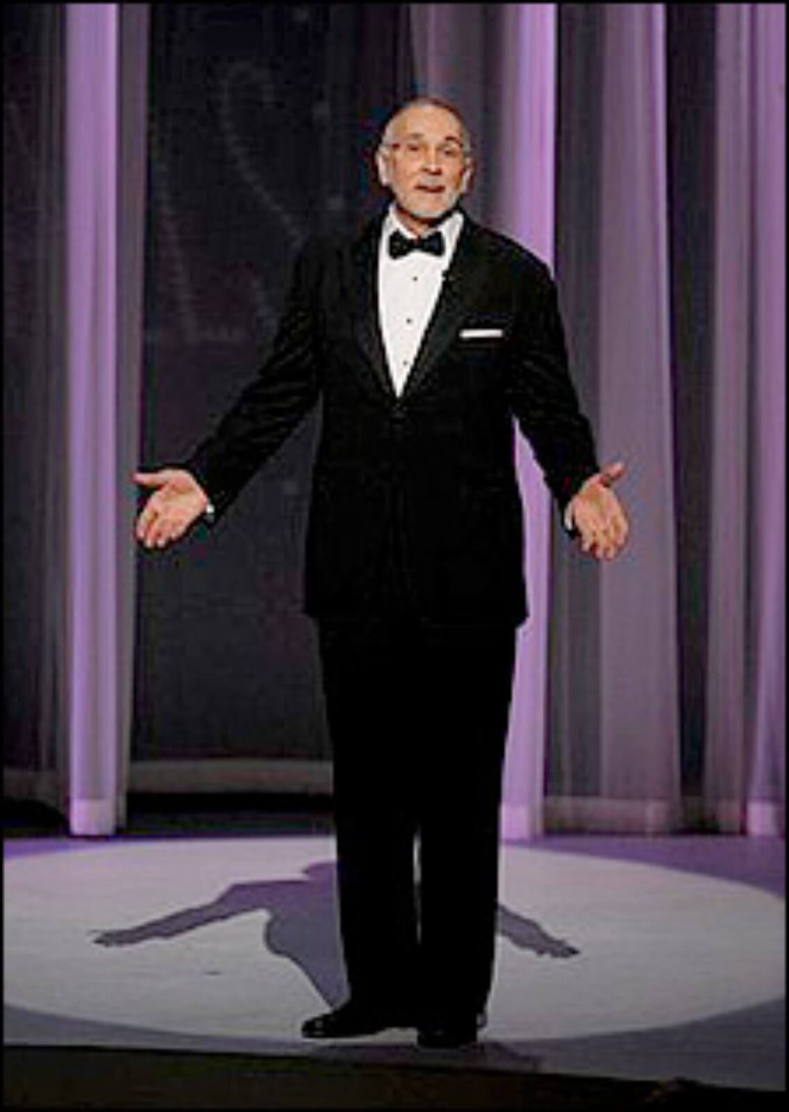 Frank Langella in front of a purple curtain wearing a tux and presenting arms forward.