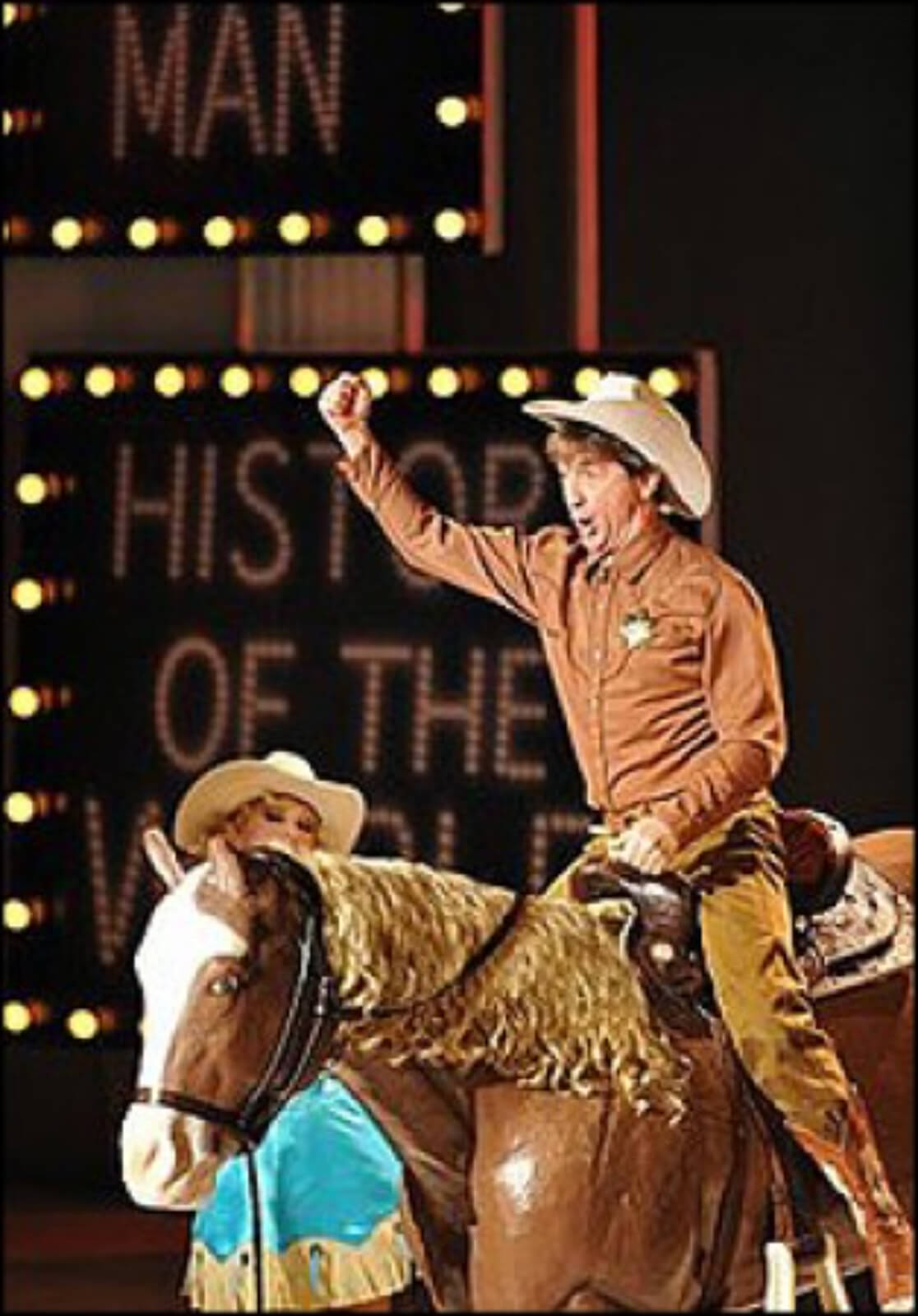 Martin Short on stage riding a horse and wearing a cowboy hat and outfit.