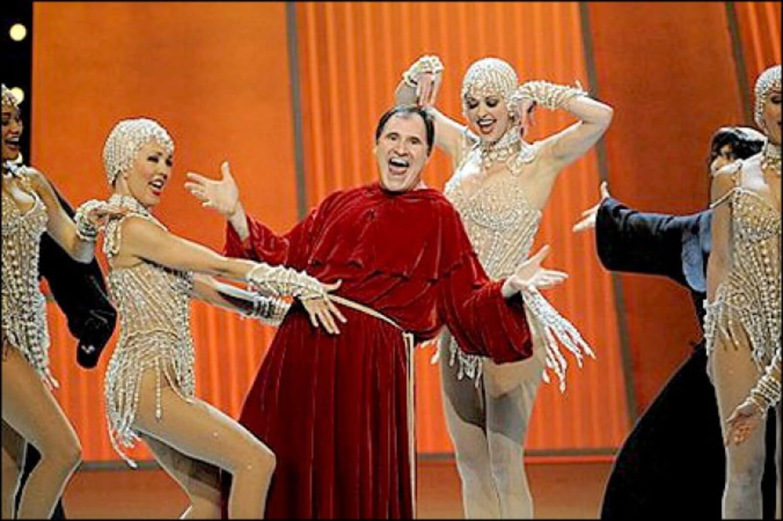 Richard Kind and The Pearl Girls. Richard is dressed as a monk while the girls dance around him. One is grabbing his belt.